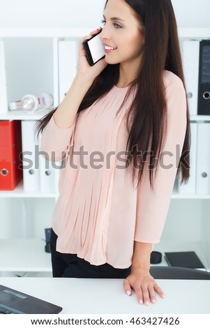 Beautiful smiling young girl talking on the mobile phone leaning on a table in the office.