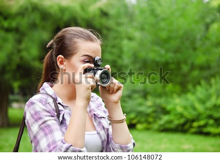 Beautiful smiling young girl with camera outdoors - stock photo