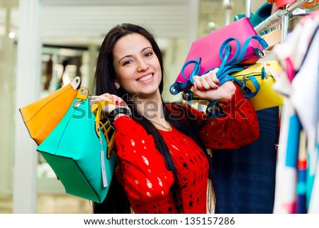 Beautiful smiling young girl with shopping bags in mall - stock photo