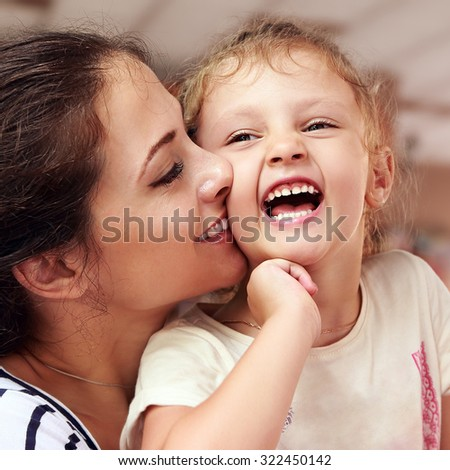 Beautiful smiling young mother hugging her joying happy daughter. Closeup portrait of people lifestyle - stock photo
