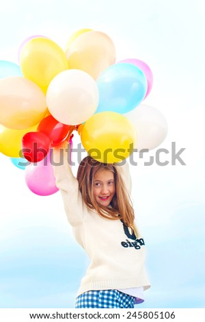 Beautiful smiling young trendy girl with bunch of colored balloons. Outdoors. Filtered image. - stock photo