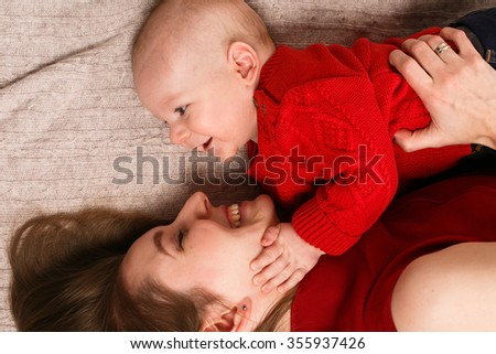 Beautiful smiling young woman in a red dress lying on the bed next to her little son in knitted red pullover