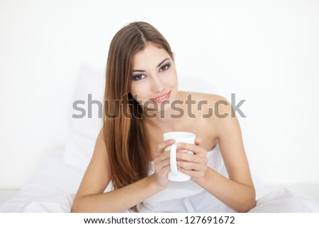 Beautiful smiling young woman in bed with a cup of coffee - stock photo