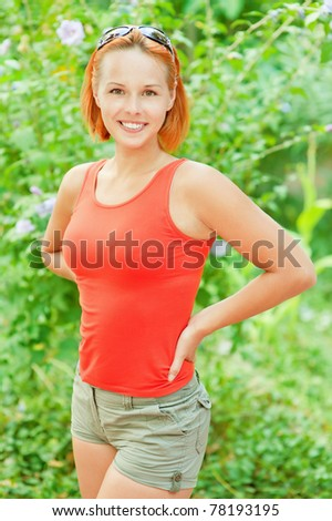 Beautiful smiling young woman in red vest and shorts against green summer garden. - stock photo