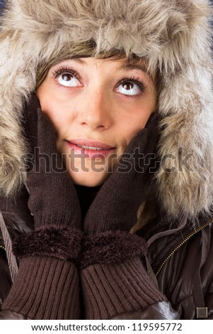 Beautiful smiling young woman in winter clothes with big bright eyes. Studio shot as a wintry close up portrait - stock photo