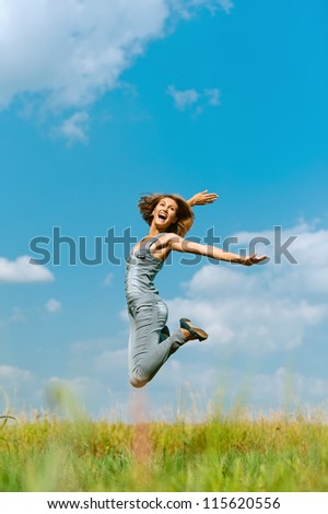 Beautiful smiling young woman jumping, against background of blue sky. - stock photo