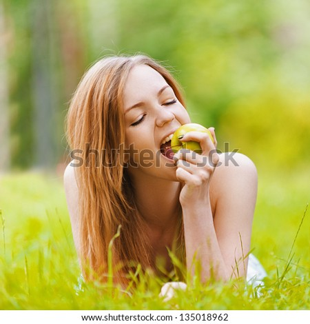 Beautiful smiling young woman lying on grass and bit apple, against background of summer green park. - stock photo