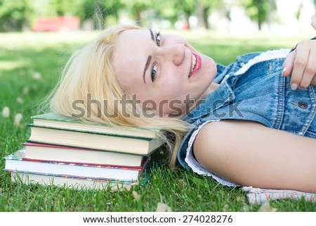 Beautiful smiling  young woman lying on grass and reading blue book, summer green park. Female student girl outside in park. Happy young university student of mixed European and Caucasian ethnicity. - stock photo
