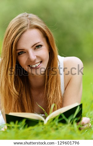 Beautiful smiling young woman lying on grass and reading book, against green of summer park. - stock photo