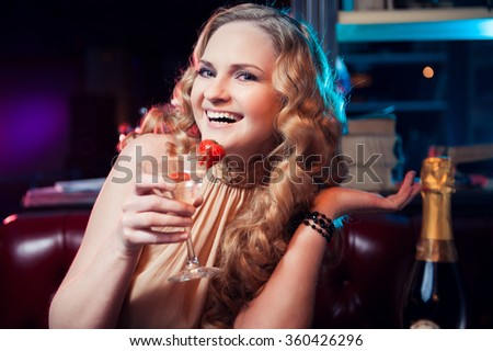 Beautiful smiling young woman portrait with martini glass drinking at  bar - stock photo