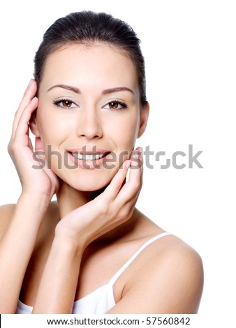 Beautiful smiling young woman stroking her clean beauty face - isolated on white - stock photo