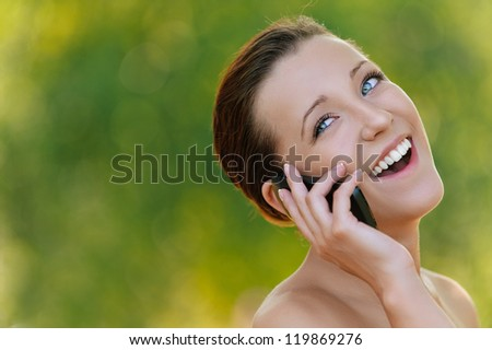 Beautiful smiling young woman talking on mobile phone, against background of summer green park. - stock photo
