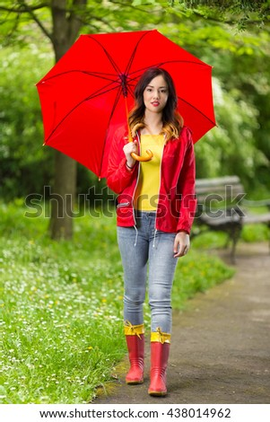 Beautiful smiling young woman walking in a park on a rainy day. She is wearing red raincoat, rubber boots and holding a red umbrella. - stock photo