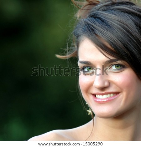 Beautiful smiling young woman with green eyes on green background 02 - stock photo