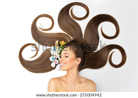 Beautiful smiling young woman with long brown hair and flowers - stock photo