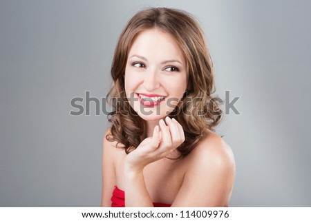 Beautiful smiling young woman with make-up and wavy hairstyle and shiny skin on grey background. Studio shot - stock photo