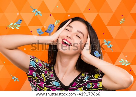 Beautiful smiling young woman, with straight dark hair, wearing on colorful shirt, posing on the orange geometric background with blue birds, in studio, waist up - stock photo
