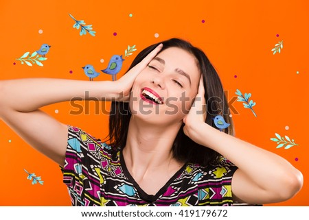 Beautiful smiling young woman, with straight dark hair, wearing on colorful shirt, posing on the orange background with blue birds, in studio, waist up - stock photo