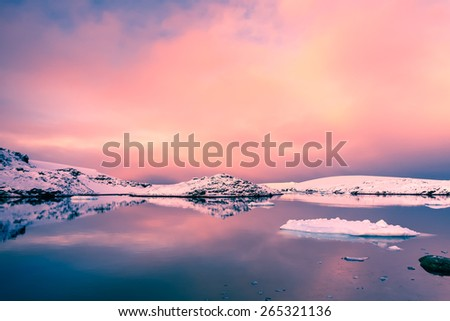 Beautiful snow-capped mountains against the sunset sky. Antarctica. Vernadsky Research Base. - stock photo