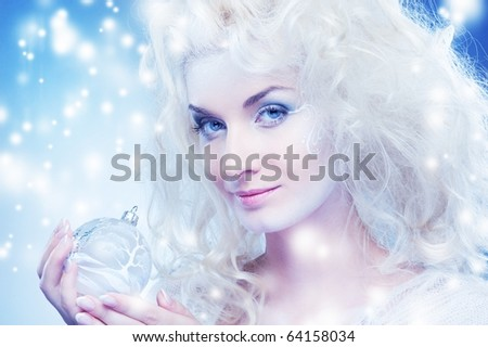 Beautiful snow queen with a christmas ball - stock photo
