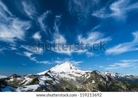 Beautiful snowcapped Mount Baker under high cirrus clouds, Washington state Cascades - stock photo