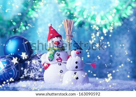 Beautiful snowmen and Christmas decor, on bright background - stock photo