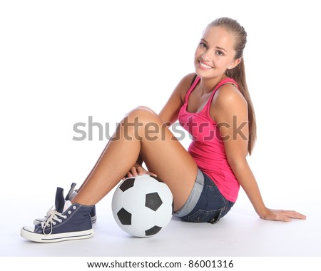 Beautiful soccer player teenage girl with happy smile wearing pink vest and denim shorts, sitting on floor with sports ball. Full body shot against white background. - stock photo