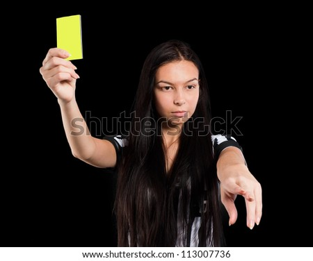 Beautiful Soccer Referee shows yellow card. Isolated on black - stock photo