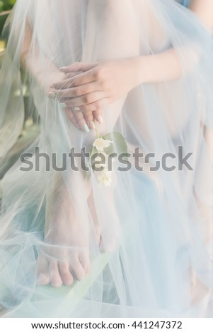 beautiful soft hands and legs of the girl with jasmine flowers in their hands sheltered blue cloth Fine art style