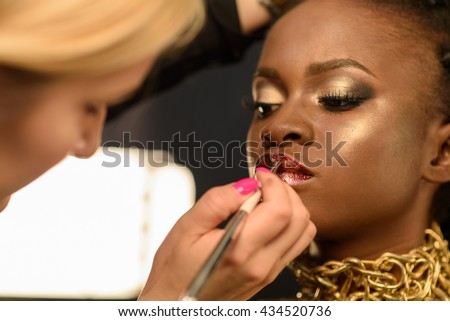 Beautiful south African woman wearing bronze necklace and natural make-up with lots of shine, makeup artist painting models lips - stock photo