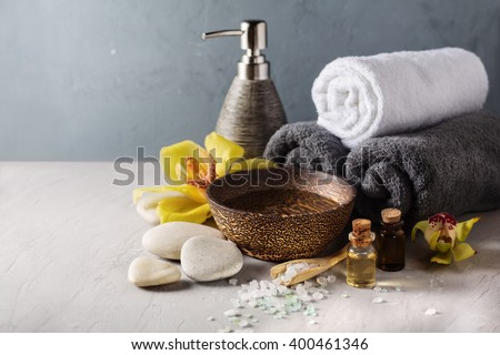 Beautiful spa composition with orchid flower and massage oil on table. SPA background with copyspace - stock photo