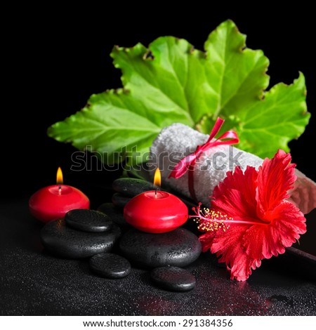 beautiful spa concept of red hibiscus flower with dew, candles, green leaf and rolled towel tied with ribbon on zen stones, closeup - stock photo