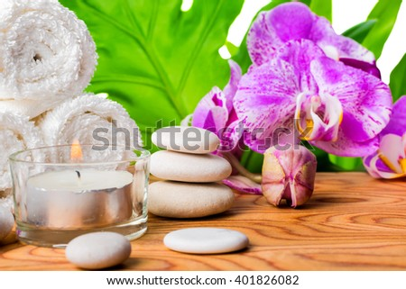 beautiful spa concept  with blooming lilac orchid, white stones, towels, candle and big green leaf on root wood background, close up  - stock photo