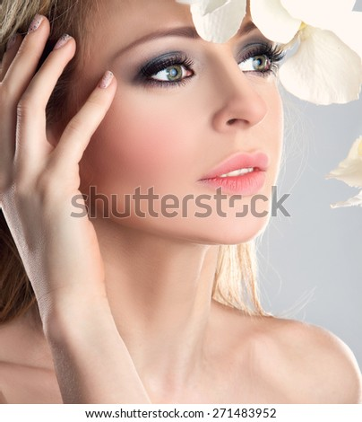 Beautiful Spa Girl With Orchid Flowers. Beauty Woman Touching her Face.  - stock photo