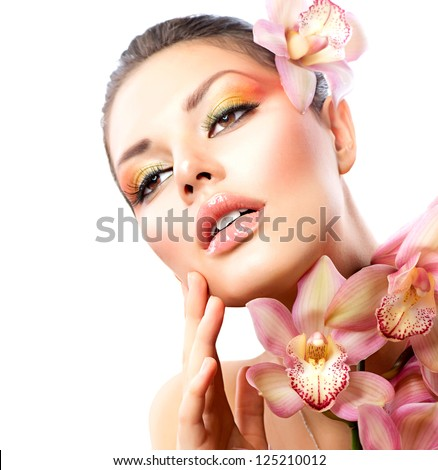 Beautiful Spa Girl With Orchid Flowers. Beauty Woman Touching her Face. Perfect Soft Skin. Skincare concept. Professional Make-up. Makeup - stock photo
