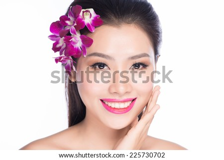 Beautiful Spa Girl With Orchid Flowers. Beauty Woman Touching her Face. Perfect Soft Skin. Skincare concept. Beauty face of beautiful woman with a white orchid flower. Skin care treatment. - stock photo