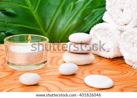 beautiful spa still life with white stones, candle, towels and big tropical green leaf on root wood background, close up  - stock photo