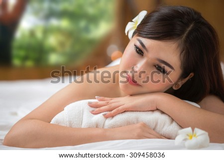 beautiful spa woman lying on the couch, out door is green nature and rolled towel - stock photo