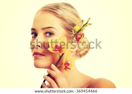 Beautiful spa woman with orange orchid - stock photo