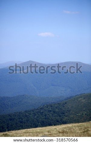 Beautiful spaciousness landscape view from hill top with dry grass on many high mountains with deep green forest and serene blue sky on natural background, vertical picture - stock photo