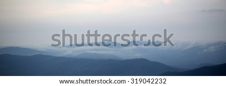 Beautiful spaciousness panoramic landscape view from high hill top on many mountain humps with deep green forests and cloudy grey blue sky on natural background, horizontal picture - stock photo