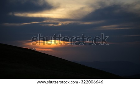 Beautiful spaciousness sunset landscape view from high hill top on cloudy grey blue yellow sky in dusk on natural evening background, horizontal picture - stock photo