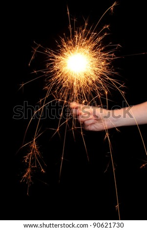 beautiful sparkler in hand on black background - stock photo