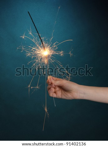 beautiful sparkler on blue background - stock photo
