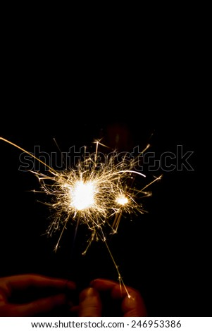beautiful sparklers in hands on black background - stock photo