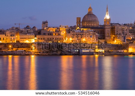 Beautiful spires and cathedral dome of the Valletta skyline under blue night sky, lights reflected in the ocean bay, Valletta, Capital city of Malta