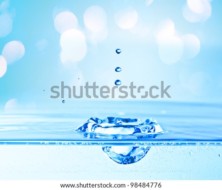 beautiful splash of water blue drops  with blue lights in the background - stock photo