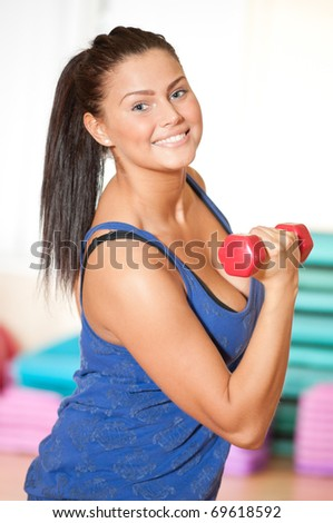Beautiful sport woman doing power fitness exercise at sport gym. Dumbbell - stock photo