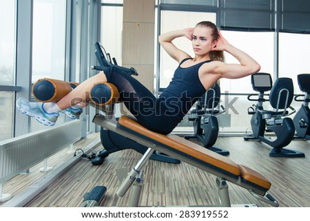 Beautiful sport woman doing press fitness exercise at gym - stock photo