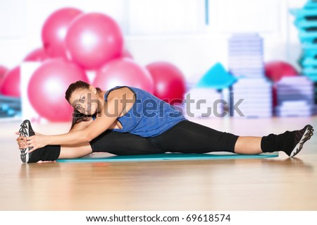 Beautiful sport woman doing stretching fitness exercise at sport gym. Yoga - stock photo